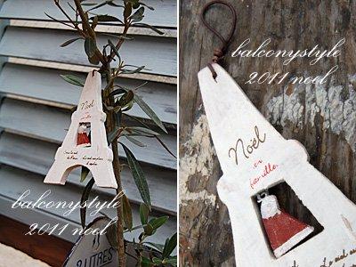 白いエッフェル塔の中でクリスマスハットが揺れる木製オーナメント